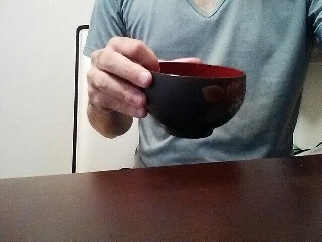 変なお茶碗の持ち方 人差し指を茶碗のふちにひっかける