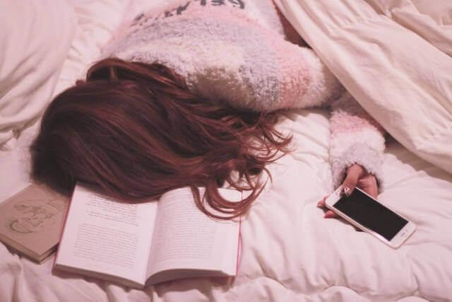寝スマホで寝落ちしている女性