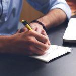 紙とペンで書いている男性